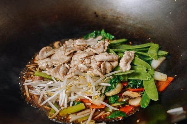Adding chicken back to wok full of vegetables, thewoksoflife.com