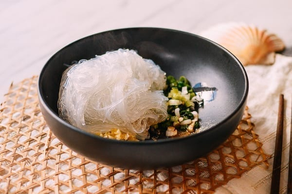 Adding cooked glass noodles to serving dish, thewoksoflife.com