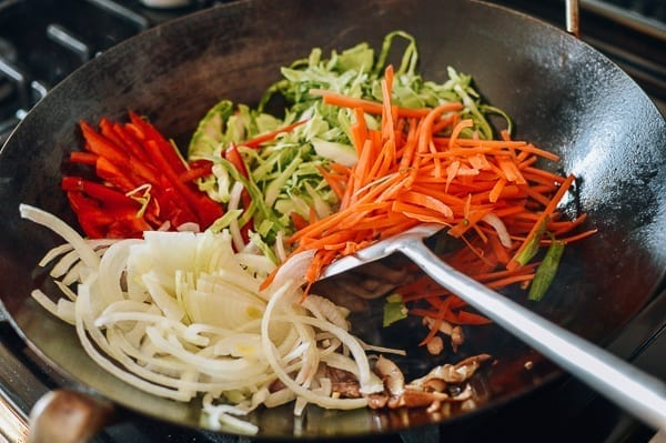 Adding cabbage, carrot, onions, and bell pepper to wok, thewoksoflife.com