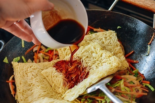 Adding yakisoba noodles and sauce, thewoksoflife.com