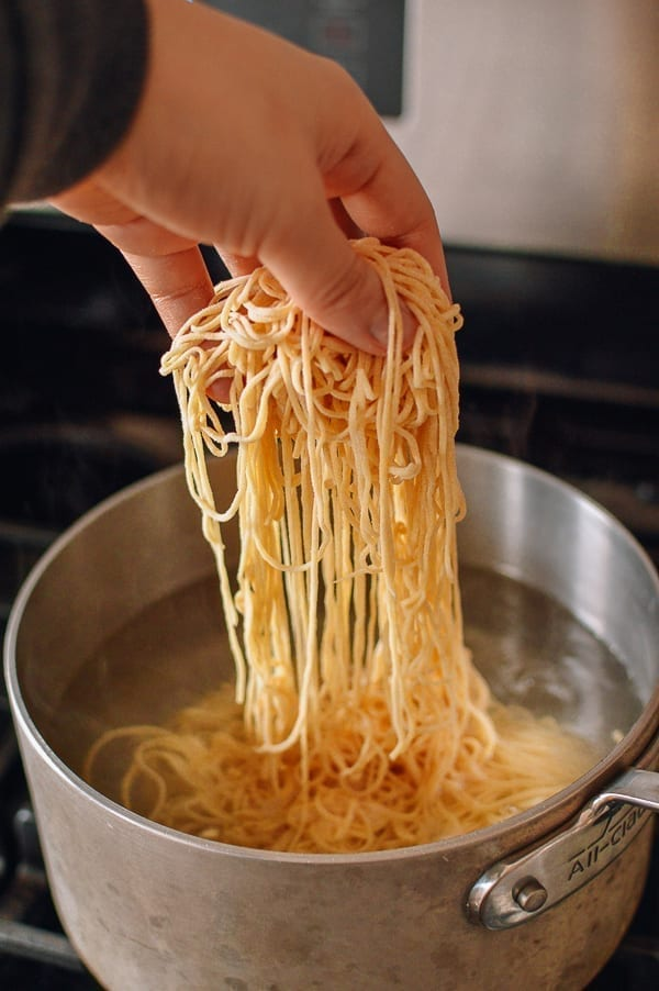 Adding noodles to boiling water, thewoksoflife.com