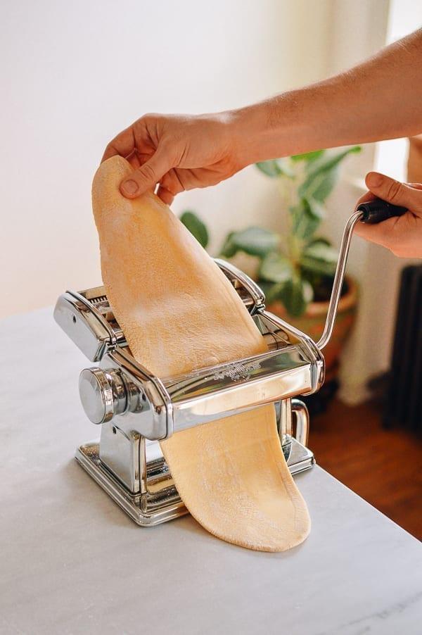 Rolling dough through pasta roller, thewoksoflife.com