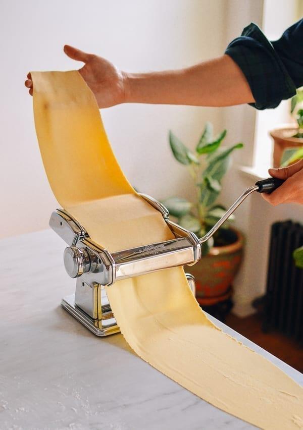Rolling dough through thin setting of pasta roller, thewoksoflife.com