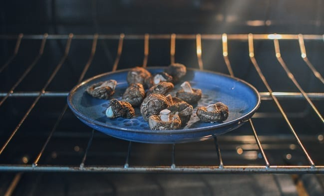 Putting mushrooms in oven to dry, thewoksoflife.com