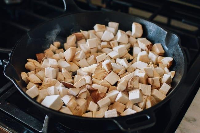 Adding mushrooms to cast iron pan, thewoksoflife.com