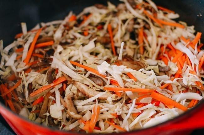 Adding vegetables to yaki udon mixture, thewoksoflife.com