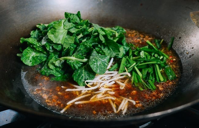 Adding pea tips to soup, thewoksoflife.com