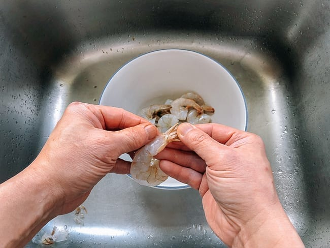 Peeling shell of shrimp tail meat, thewoksoflife.com