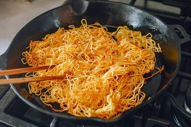 Breaking up fried noodles with chopsticks, thewoksoflife.com