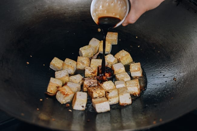 Adding light soy sauce to tofu, thewoksoflife.com