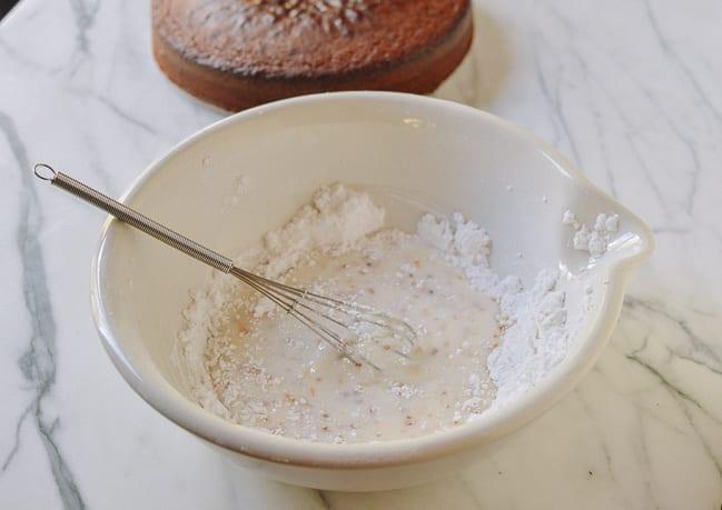 Making osmanthus glaze with powdered sugar, milk, and osmanthus syrup, thewoksoflife.com