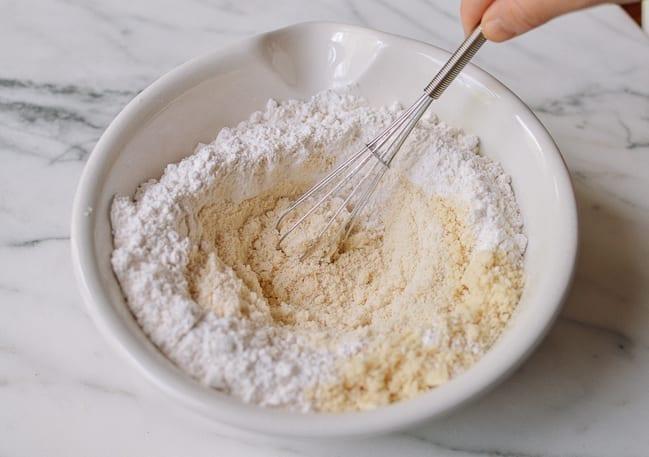 Whisking together almond flour, self-rising flour, and salt, thewoksoflife.com