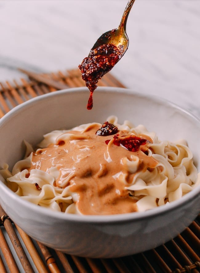 Adding extra chili oil to peanut noodles, thewoksoflife.com