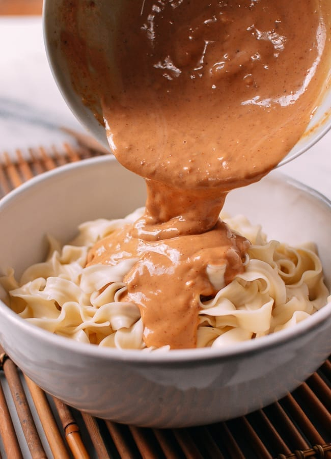Pouring sauce over noodles, thewoksoflife.com