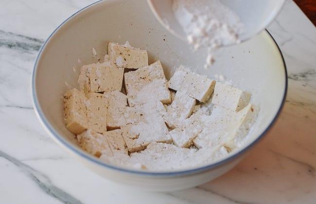 Adding spiced flour and cornstarch dredge to tofu, thewoksoflife.com