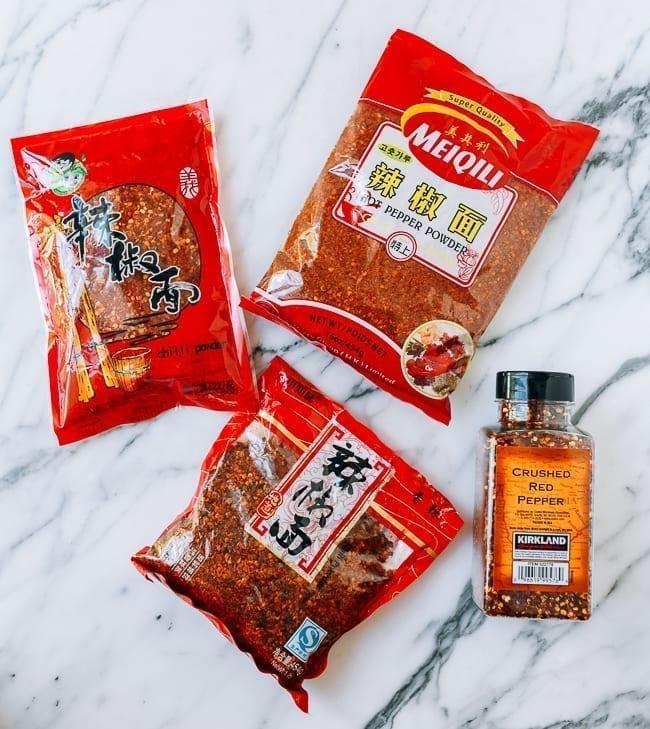Sichuan chili flakes next to regular crushed red pepper, thewoksoflife.com