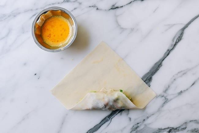 Rolling corner of egg roll wrapper over filling, thewoksoflife.com