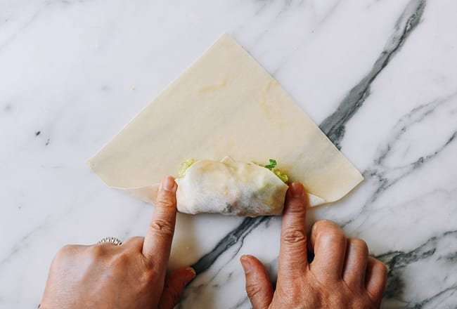 Pressing down egg roll wrapper on both sides of filling, thewoksoflife.com