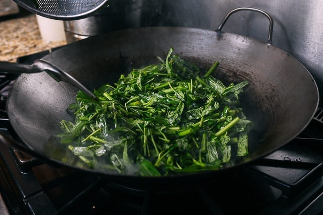 Adding water spinach to wok
