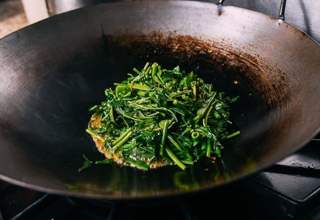 Piling water spinach in center of wok