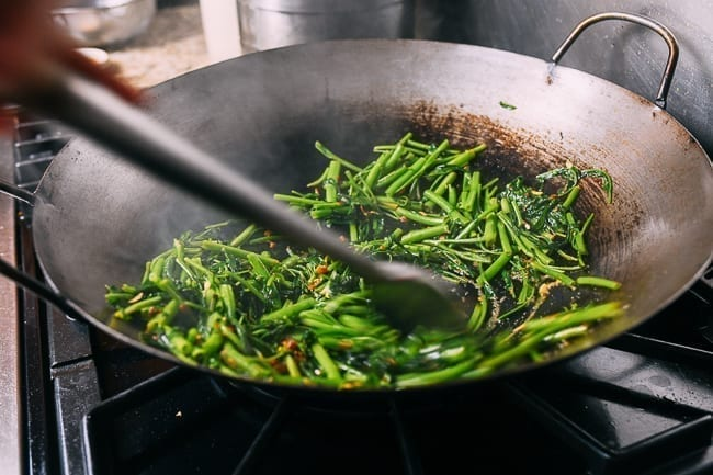 Stir-frying water spinach on hot sides of wok