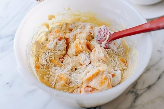 Folding flour, peaches, and nuts into batter, thewoksoflife.com