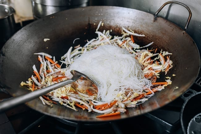 Adding the rice noodles to the wok, thewoksoflife.com