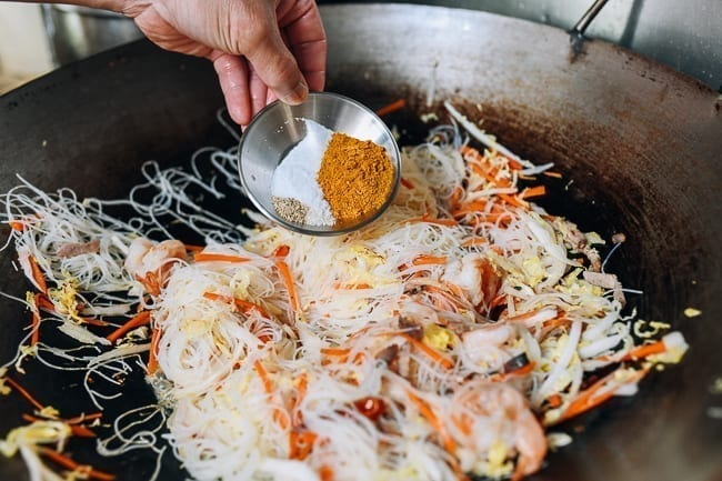 Adding curry powder, salt, sugar, and white pepper to noodles in wok, thewoksoflife.com