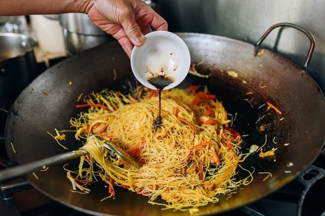 Adding sesame oil and soy sauce to singapore noodles in wok, thewoksoflife.com