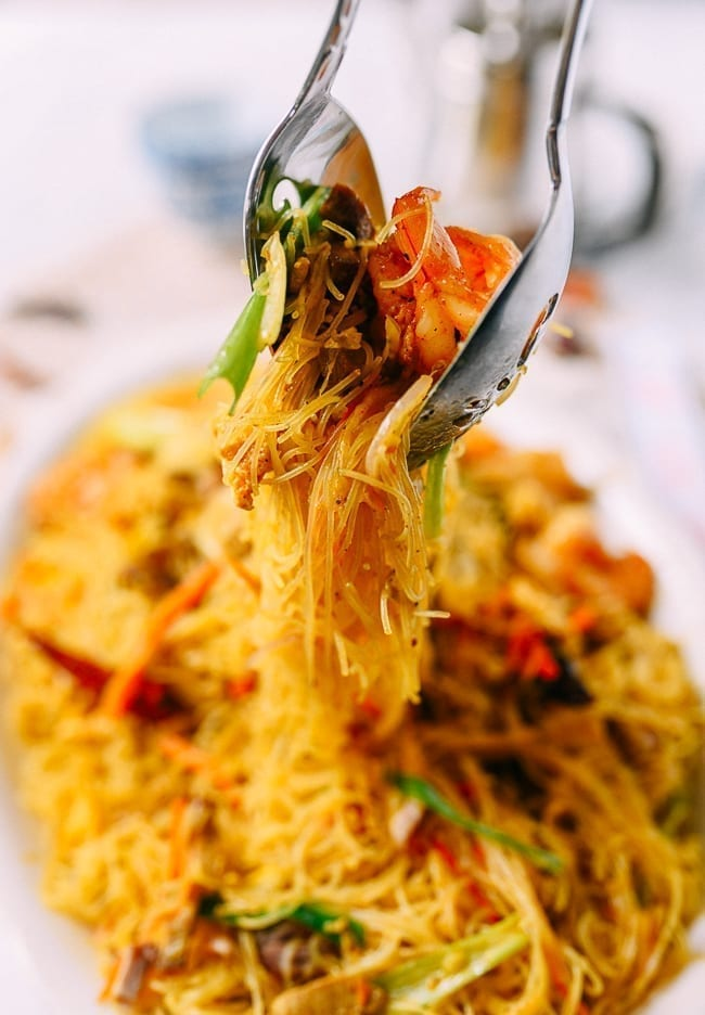 Lifting Singapore noodles off plate with two spoons, thewoksoflife.com