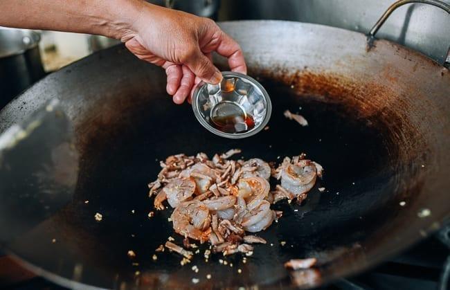 Adding Shaoxing wine to shrimp and pork, thewoksoflife.com