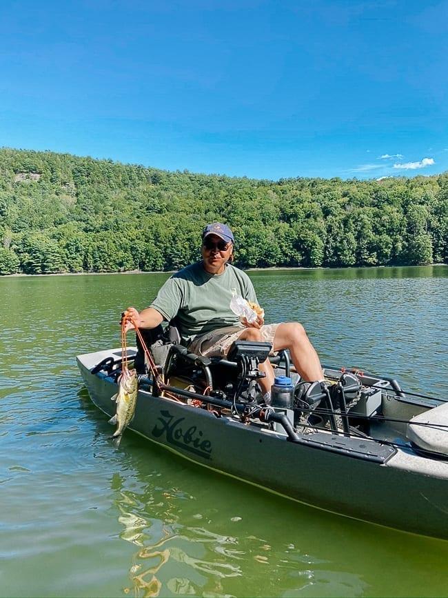 Bill on fishing kayak holding catch, thewoksoflife.com