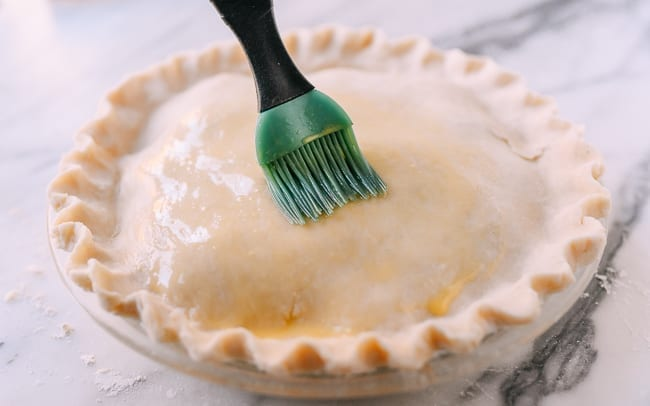 Brushing pie crust with egg wash, thewoksoflife.com