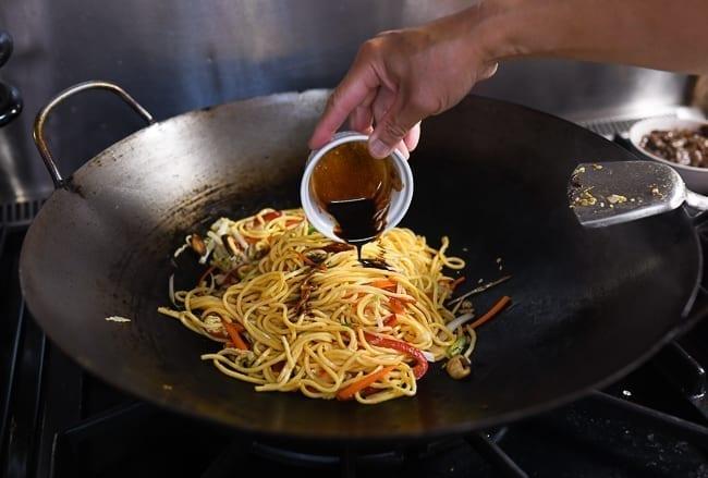 Adding pre-mixed sauce to lo mein in wok, thewoksoflife.com