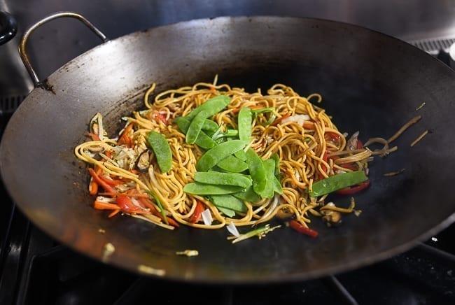 Adding snow peas to lo mein, thewoksoflife.com