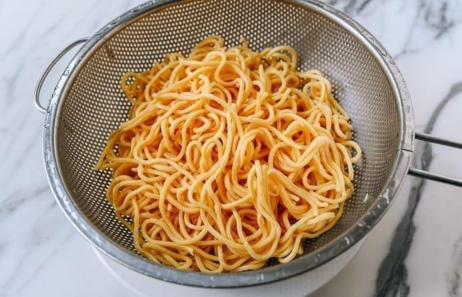 Lo mein noodles in a colander, thewoksoflife.com