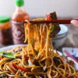 Picking up beef lo mein with chopsticks, thewoksoflife.com
