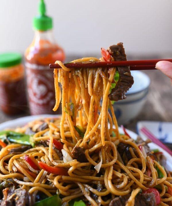 Picking up beef lo mein with chopsticks, thewoksoflife.com