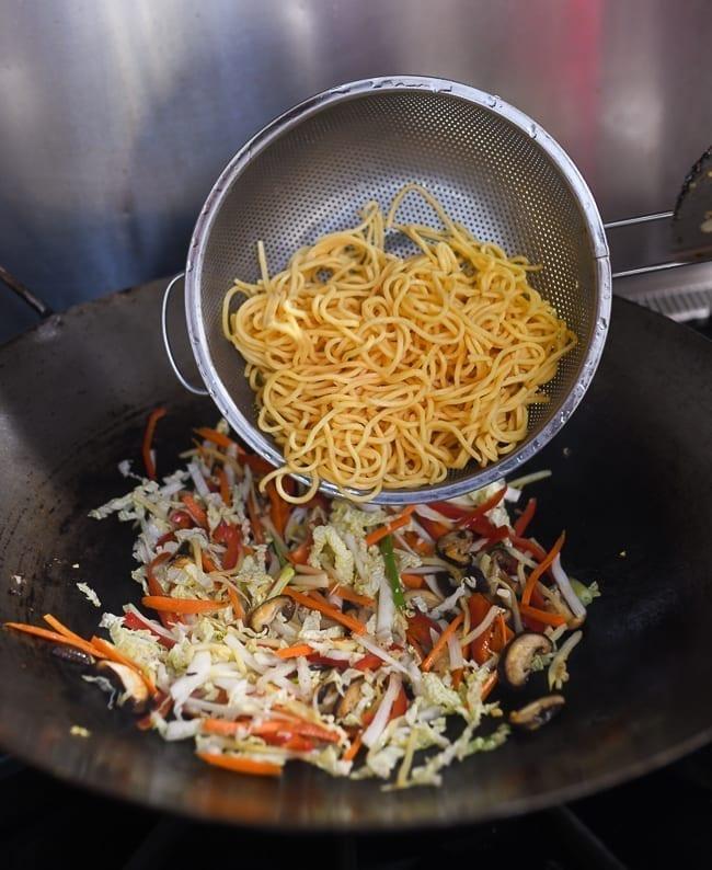Adding lo mein noodles to vegetables in wok, thewoksoflife.com
