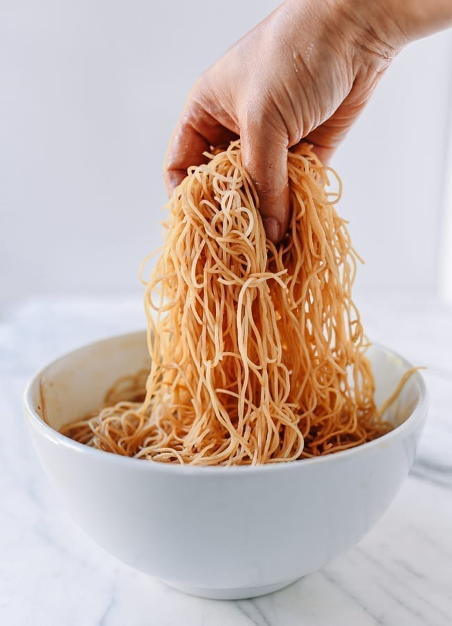 Mixing soaked rice noodles with dark soy sauce and oil, thewoksoflife.com