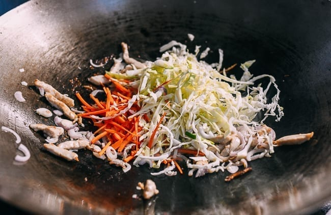 Adding cabbage and carrots to the stir-fry, thewoksoflife.com