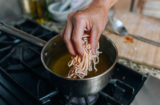Dropping small handful of egg noodles into hot oil
