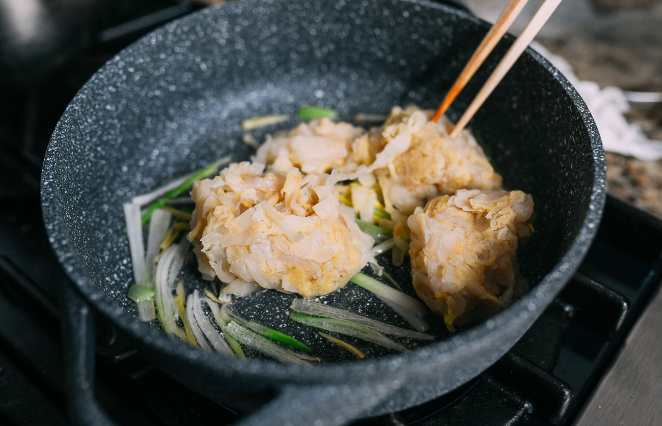 Adding sour cabbage to ginger and scallions