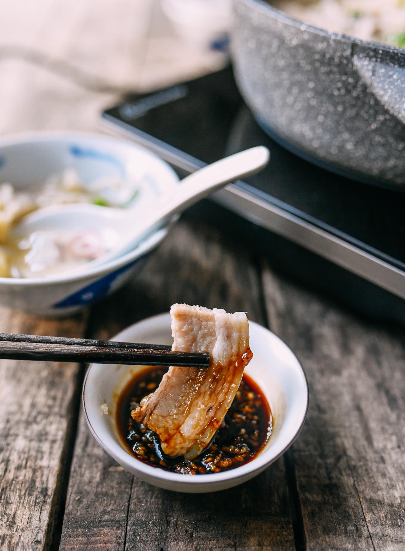 Dipping pork belly into garlic soy dipping sauce