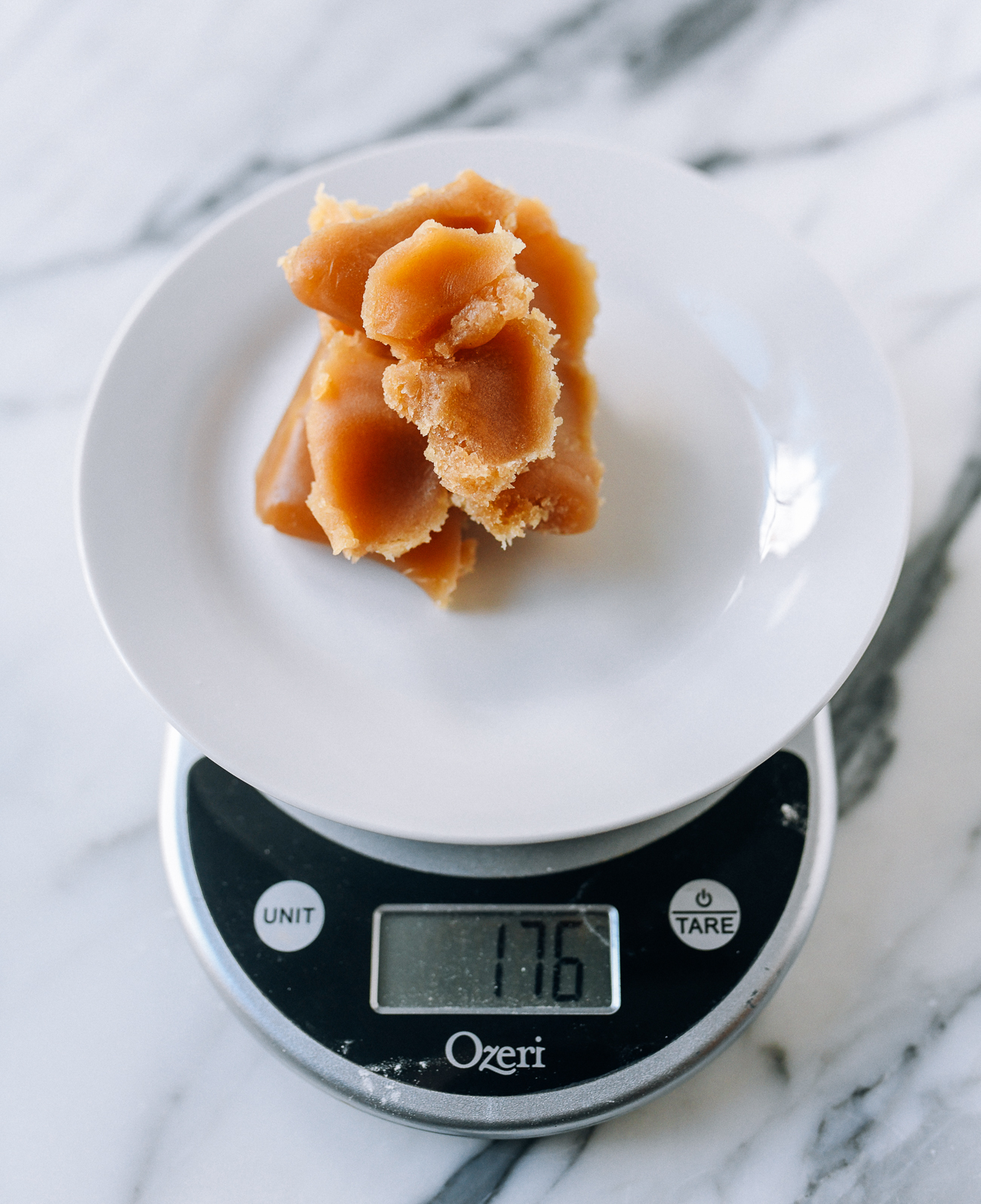 Measuring lotus paste on digital kitchen scale