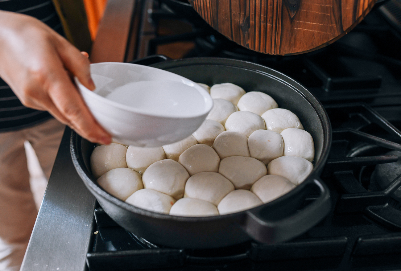 Adding water to pan of Shengjian Bao, thewoksoflife.com