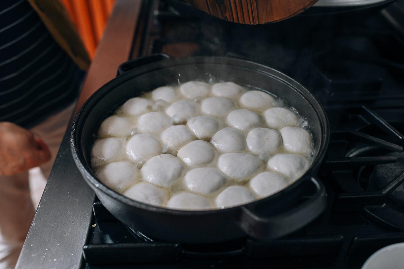 Water sizzling and bubbling in pan of Shengjian bao, thewoksoflife.com