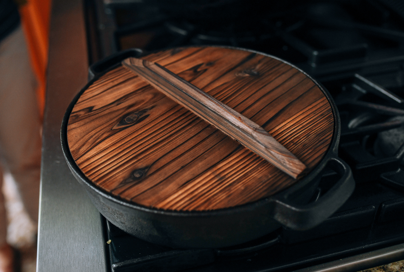 Chinese-style cast iron pan covered with wooden lid, thewoksoflife.com