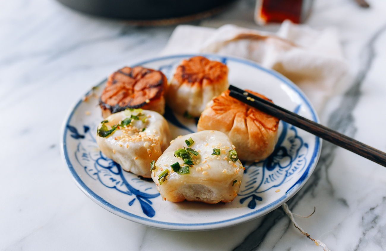Plate of golden brown shengjian bao, thewoksoflife.com