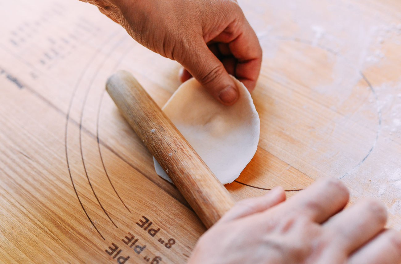 Rolling shengjian bao dough into round circles using a Chinese rolling pin, thewoksoflife.com